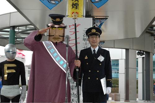 高津消防署長の横で敬礼するヴァンプ将軍 (C)くぼたまこと/スクウェアエニックス・フライングドッグ