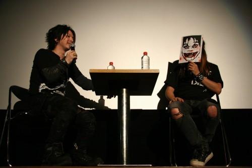 映画の内容に合わせお面に血をたらしたカトウタロウ氏(右) (c)Listen Japan