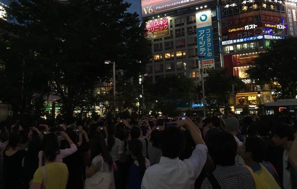 東京・渋谷のスクランブル交差点付近の街頭ビジョンでの生中継告の様子 (okmusic UP's)